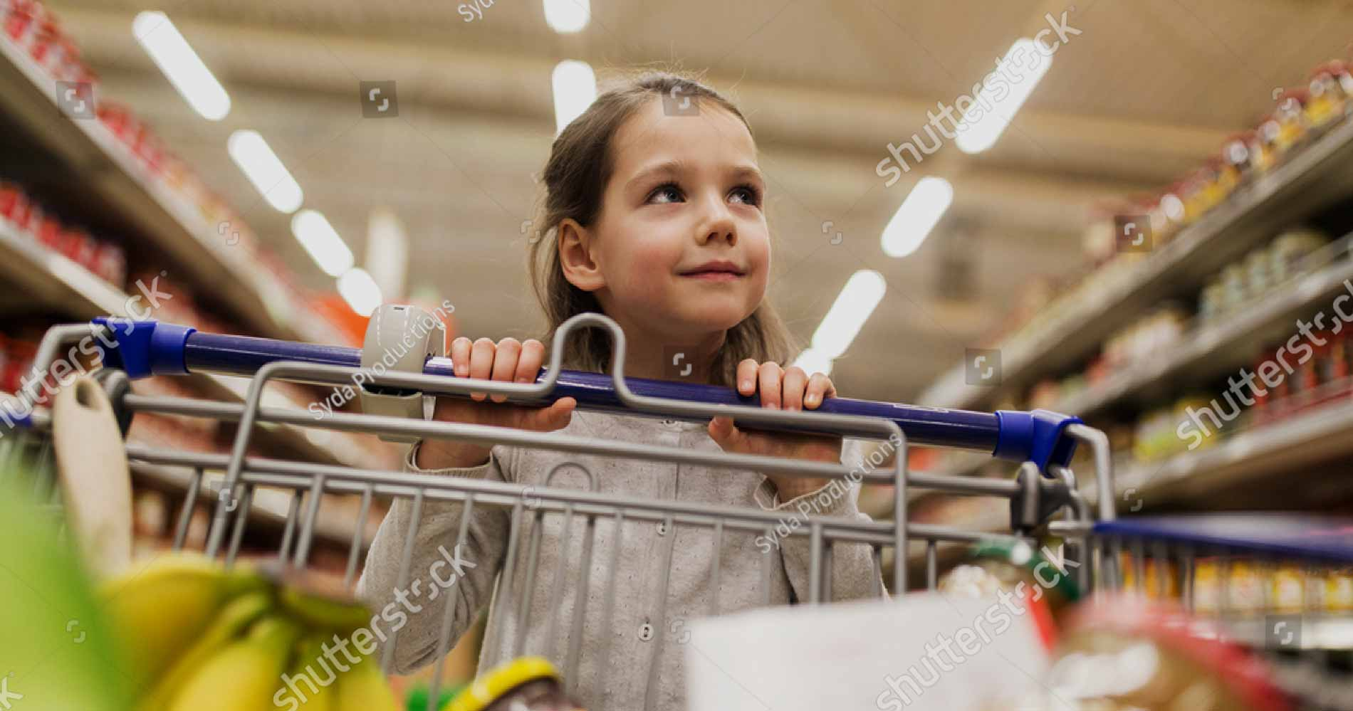 sale-consumerism-and-people-concept-happy-little-girl-with-food-in-shopping-cart-at-grocery-store